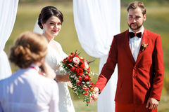 The wedding ceremony, bride and groom give oaths listen to speaker. Sunny summer day. color style decoration red marsala Stock Images