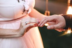Wedding ceremony. The bride in a pink dress wears an engagement ring on a finger to the groom. On her hand is a gold ring with a d. Iamond close-up. Horizontal stock photo