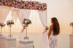 Wedding ceremony. Brunette bride standing by wreath arch with fl Stock Images