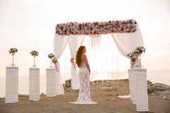Wedding ceremony. Brunette bride under wreath arch with flower a. Rrangement and white curtain on cliff above sea, outdoor photo. Bridal day. Sunset Stock Photos