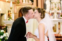 Wedding ceremony in catholic church. First kiss. Marriage vow. Wedding day Royalty Free Stock Photos