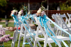 Wedding ceremony chairs and a bouquet of roses Stock Image
