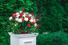 Wedding ceremony. Column, decorated with bouquet of red and white roses, in the wedding ceremony area. Trees on a background Stock Image
