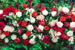 Wedding ceremony. Column, decorated with bouquet of red and white roses, in the wedding ceremony area. Trees on a background Stock Photo