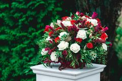 Wedding ceremony. Column, decorated with bouquet of red and white roses, in the wedding ceremony area. Trees on a background Royalty Free Stock Photo