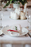 Wedding ceremony decoration in the restoraunt. The composition of green sprig eucalyptus flowers on festive table with white table. Wedding ceremony decoration Stock Photo