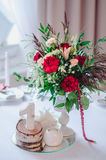 Wedding ceremony decoration in restoraunt. The composition of red and pink flowers, green stands on table with white tablecloth, w Stock Photo