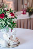 Wedding ceremony decoration in restoraunt. The composition of red and pink flowers, green stands on table with white tablecloth, w Royalty Free Stock Photography