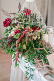 Wedding ceremony decoration in restoraunt. The composition of red and pink peonies, rose flowers, eucalyptus green stands on table Stock Image