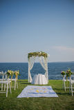 Wedding ceremony flowers, arch, chairs with black sea in the background. Beach wedding. Wedding ceremony flowers, arch, chairs with black sea in the background Royalty Free Stock Photography