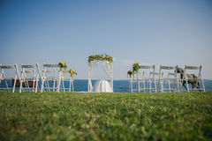 Wedding ceremony flowers, arch, chairs with black sea in the background. Beach wedding. Wedding ceremony flowers, arch, chairs with black sea in the background Royalty Free Stock Images