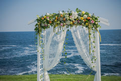 Wedding ceremony flowers, arch, chairs with black sea in the background. Beach wedding. Wedding ceremony flowers, arch, chairs with black sea in the background Stock Photos