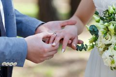 Wedding ceremony. The groom places the ring on the bride`s hand. Photo closeup Stock Images