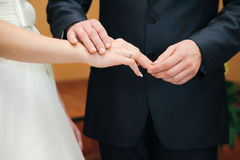 Wedding ceremony. Groom put on ring upon a bride fingers Stock Photos