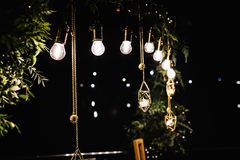 Garlands of lamps on a wooden stand on the street. A wedding Ban stock photography