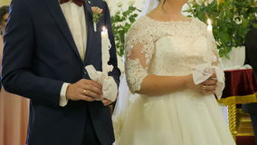 Wedding ceremony in orthodox church. Bride and groom holding the candles. Close up. Wedding ceremony in orthodox church. Bride and groom holding the candles stock footage