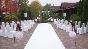 Wedding ceremony outdoors. Chairs in covers stock video footage