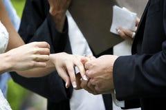 Wedding ceremony ring exchange. Putting the ring on the bride during a wedding ceremony royalty free stock photo