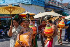 Wedding ceremony on the street. Young attractive women in traditional dresses and jewelery stand under umbrellas and hold bouquets. Ayutthaya, Thailand - March 3 royalty free stock photo