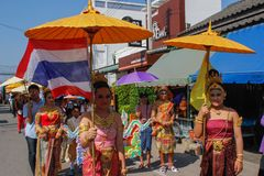 Wedding ceremony on the street. Young attractive women in traditional dresses and jewelery stand under umbrellas and hold bouquets. Ayutthaya, Thailand - March 3 stock photography