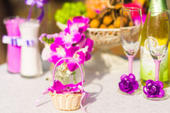 Wedding ceremony in Thailand. Composition of little basket with wedding rings, wine glasses and tropical flowers and fruits, and sand ceremony glasses Royalty Free Stock Images