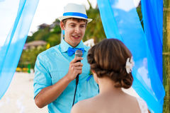 Wedding ceremony on a tropical beach in blue . The groom speaks Stock Images