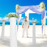 Wedding ceremony on a tropical beach in blue.The groom waits for Royalty Free Stock Images