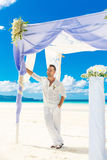 Wedding ceremony on a tropical beach in blue.The groom waits for Stock Image