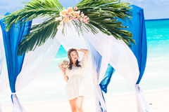 Wedding ceremony on a tropical beach in blue. Happy bride with a Royalty Free Stock Photography