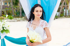 Wedding ceremony on a tropical beach in blue. Happy bride under Royalty Free Stock Photo
