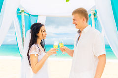 Wedding ceremony on a tropical beach in blue. Happy groom and br Stock Image