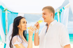 Wedding ceremony on a tropical beach in blue. Happy groom and br Stock Images