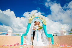 Wedding ceremony on a tropical beach in blue. Happy groom and br Royalty Free Stock Photos