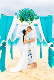 Wedding ceremony on a tropical beach in blue. Happy groom and br Stock Photo