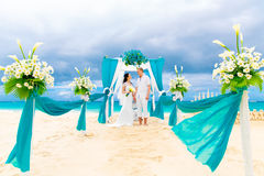 Wedding ceremony on a tropical beach in blue. Happy groom and br. Ide under the arch decorated with flowers on the sandy beach. Wedding and honeymoon concept Stock Photos