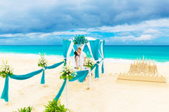 Wedding ceremony on a tropical beach in blue. Happy groom and br Royalty Free Stock Photography