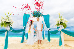 Wedding ceremony on a tropical beach in blue. Happy groom and br Royalty Free Stock Images