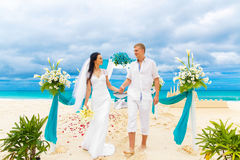 Wedding ceremony on a tropical beach in blue. Happy groom and br Royalty Free Stock Photo