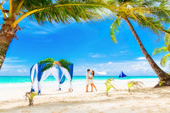 Wedding ceremony on a tropical beach in blue. Happy groom and br. Ide under the arch decorated with flowers on the sandy beach. Wedding and honeymoon concept Stock Image