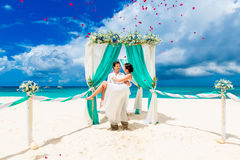 Wedding ceremony on a tropical beach in blue. Happy groom and br Royalty Free Stock Image