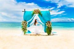 Wedding ceremony on a tropical beach. Happy bride under the wedd Stock Photos