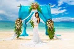 Wedding ceremony on a tropical beach. Happy bride under the wedd Stock Photo