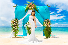 Wedding ceremony on a tropical beach. Happy bride under the wedding arch Stock Photo