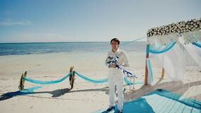 Wedding ceremony on a tropical beach among palm trees and the ocean. A stylish happy bridegroom with a bouquet of white. And blue flowers stands near the arch stock footage