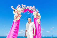 Wedding ceremony on a tropical beach in purple. The groom waits Royalty Free Stock Photos