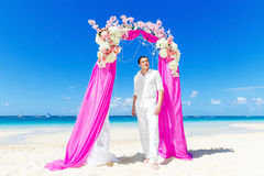 Wedding ceremony on a tropical beach in purple. The groom waits Stock Image