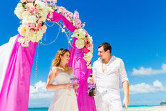 Wedding ceremony on a tropical beach in purple. Happy groom and Stock Photography