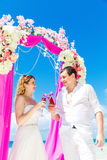 Wedding ceremony on a tropical beach in purple. Happy groom and Stock Images