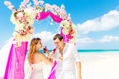 Wedding ceremony on a tropical beach in purple. Happy groom and Stock Photo