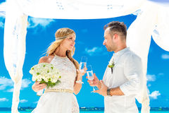 Wedding ceremony on a tropical beach in white. Happy groom and b Stock Photography
